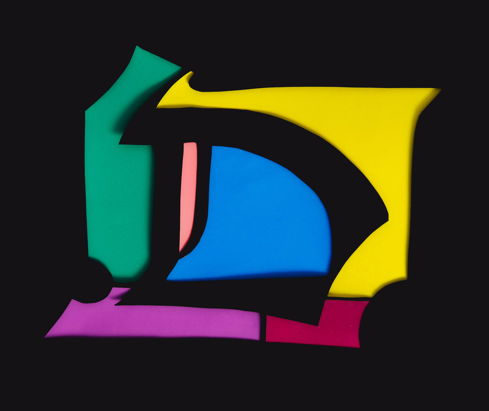 """Paper Cut-Out """"D"""" - A Rudolf Koch inspired blackletter D. Black paper cutout with bright colored paper backgrounds."""