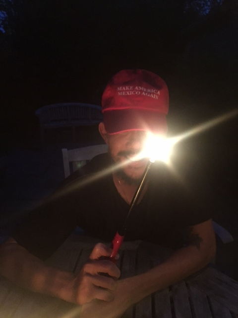A friend, wearing a baseball cap that pokes fun of Trump's campaign propaganda.
