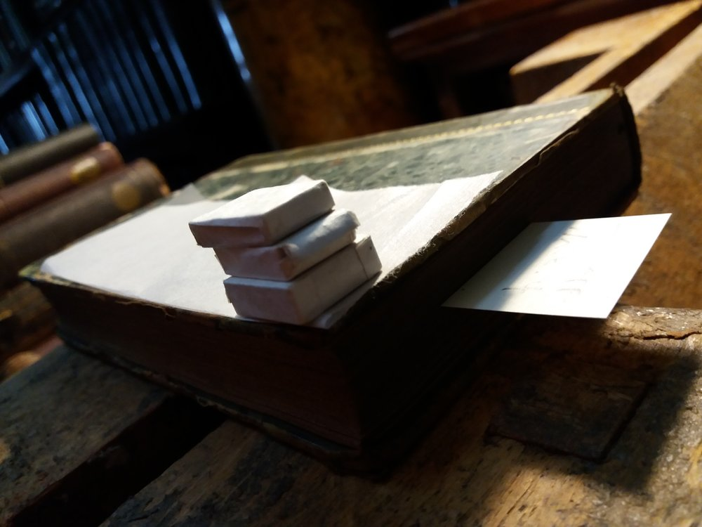 Small weights on one of the repaired books.