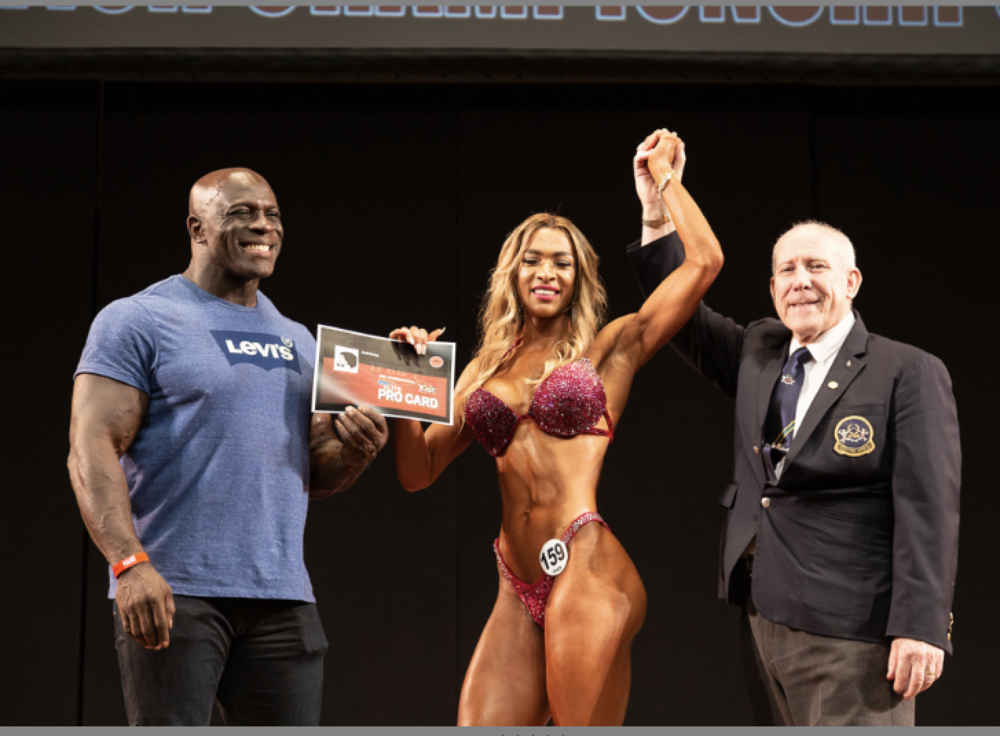 Wellness winner Alaura Galeru celebrates turning pro with Eddie Abbew (left) and UKBFF president Bill Tierney. Pic by Kevin Horton