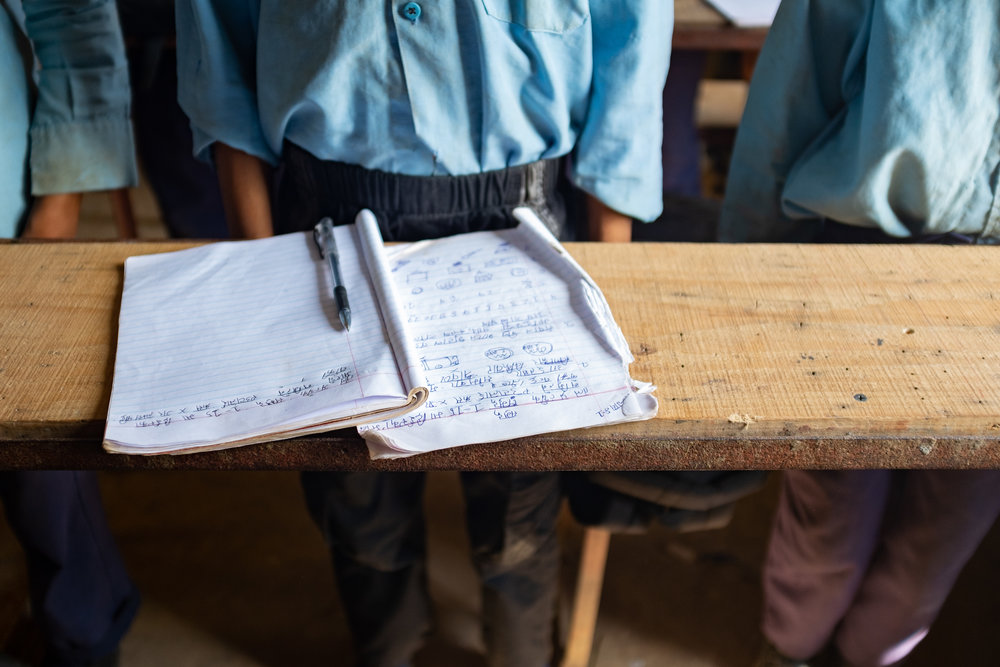 A student displays his writing notebook at a Nazarene child development center in Lower Bhotsipa.