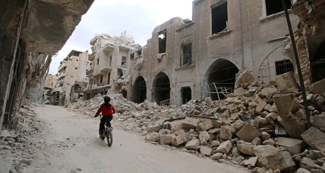 A boy rides his bicycle amid ruins in war-torn Aleppo (Reuters Photo)