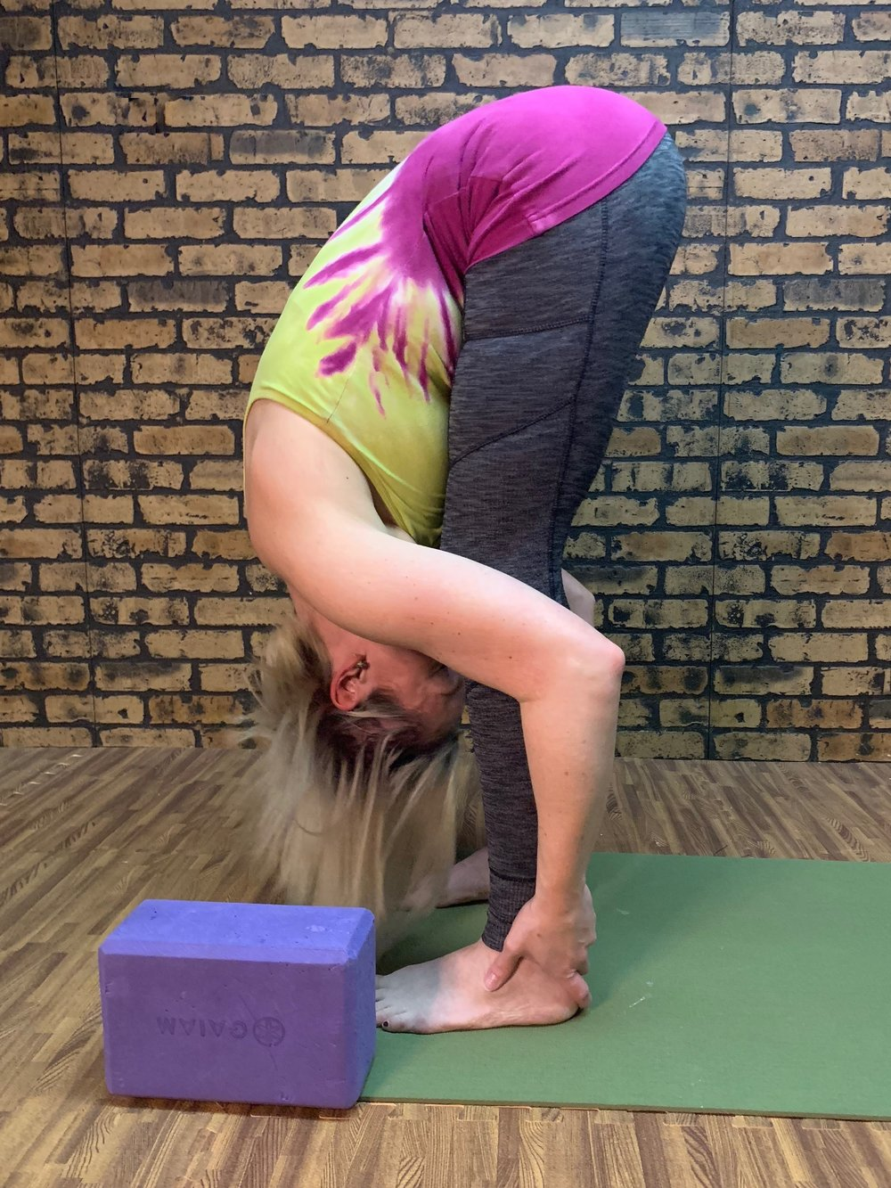 """(Exhale) """"Swan dive"""" into a forward bend (Uttanasana). You may bend your knees generously if your hamstrings are tight to keep your low back safe. Let your head drop.Gaze is inward."""