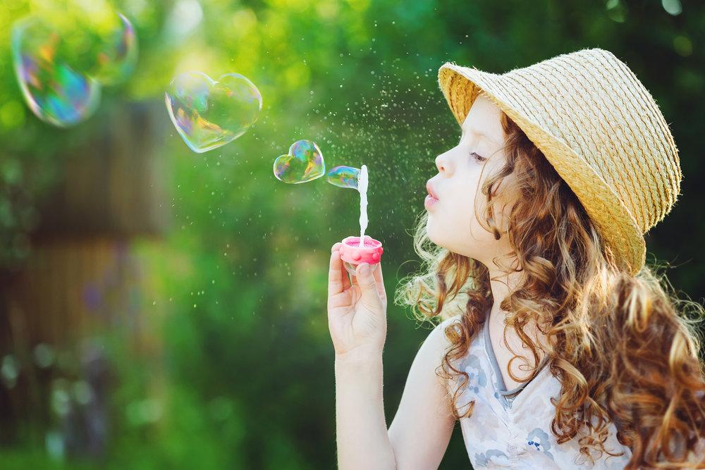 bigstock-Little-Girl-Blowing-Soap-Bubbl-108826970.jpg