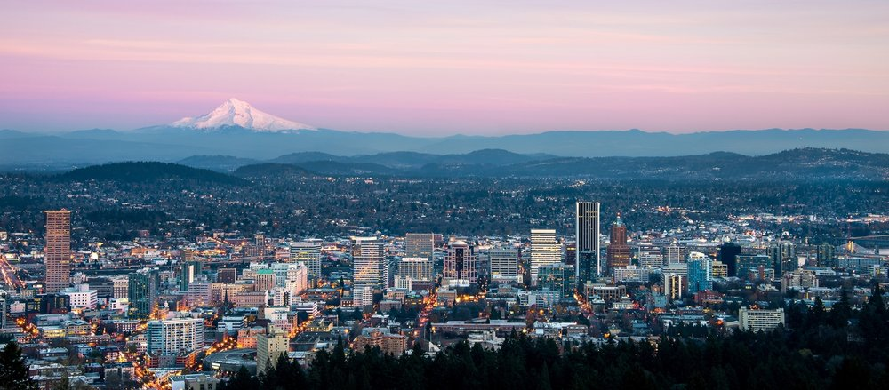 Downtown Portland, Oregon USA on a spring evening looking east towards the 11,250 foot high Mt Hood,  50 miles in the distance.  Taken atop the city's tallest locale, the 1,000 foot high Council Crest in the West Hills of Portland.