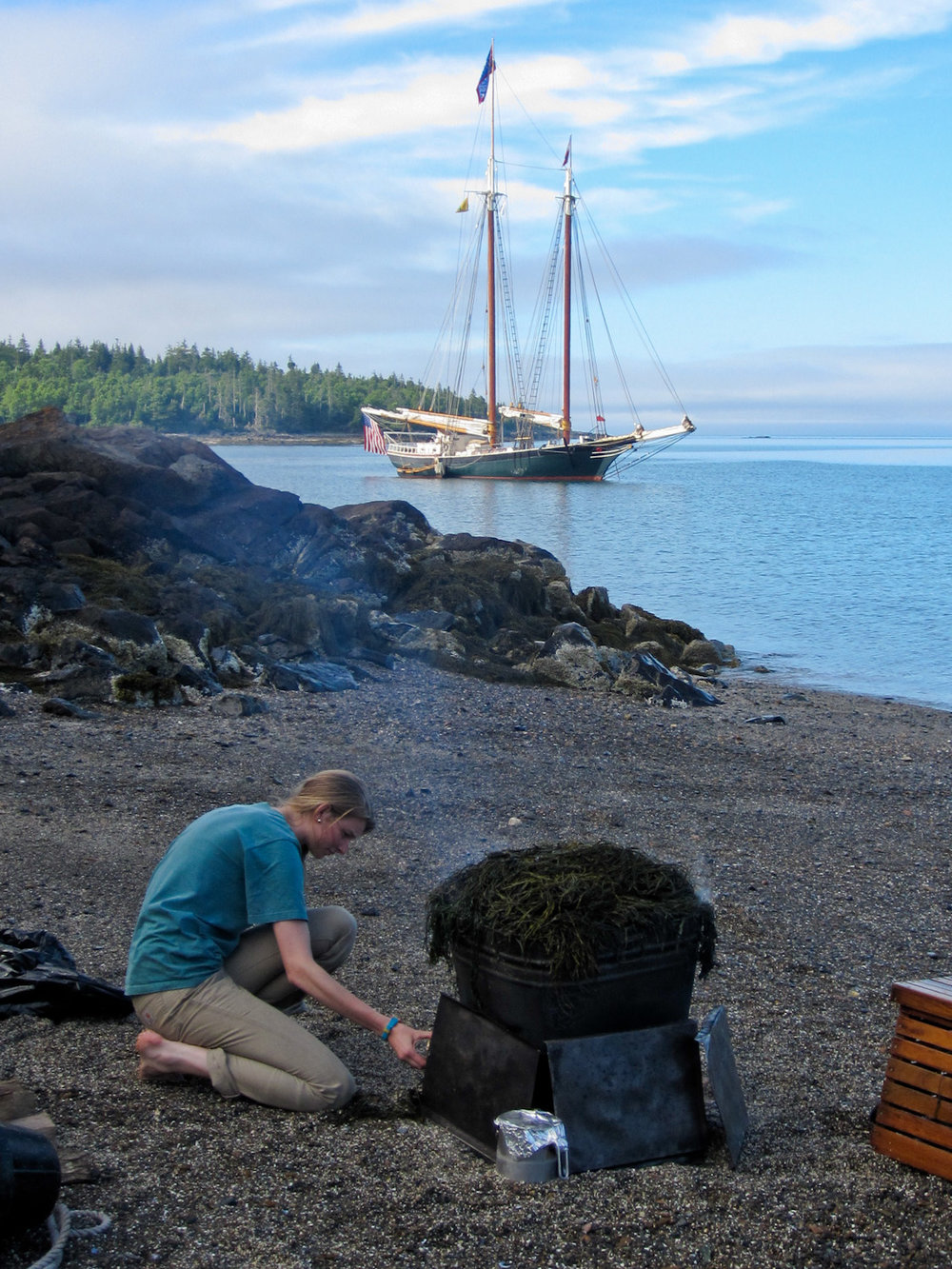 Keeping the fire stoked under the lobsters and corn on the cob as the  Taber  sits anchored off shore.