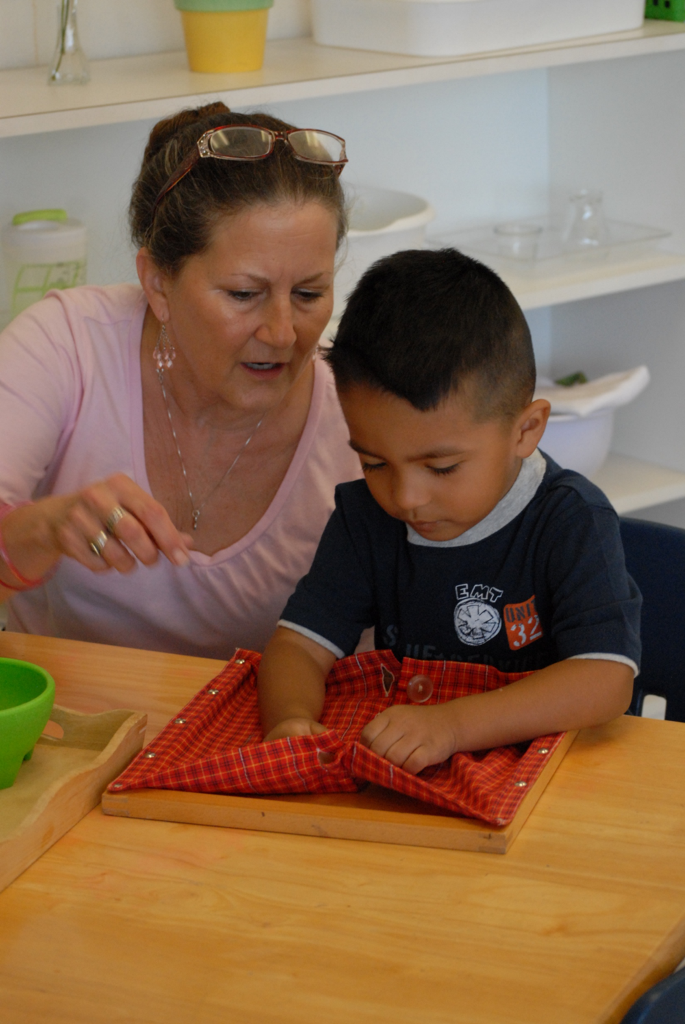 """Figure 2 - Gently guided by his teacher, this student is using a """"dressing frame"""" to learn how to button."""