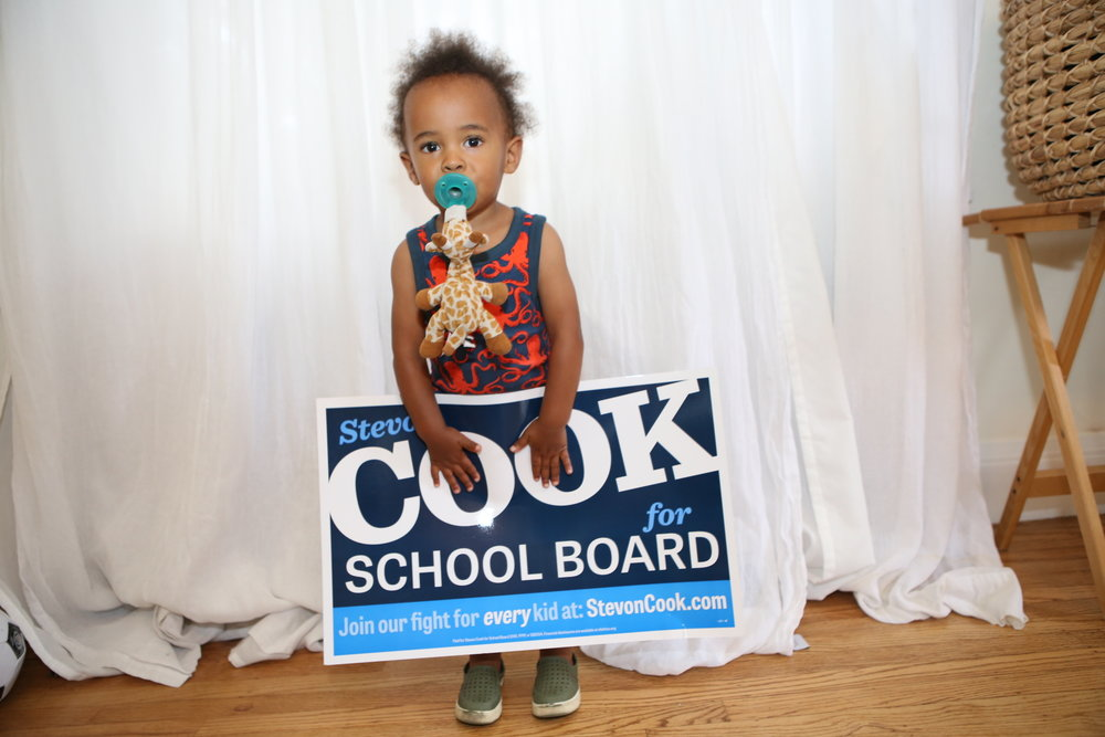 Stevon Cook's nephew Lathan taking a photo with a Cook for School Board sign in 2016.