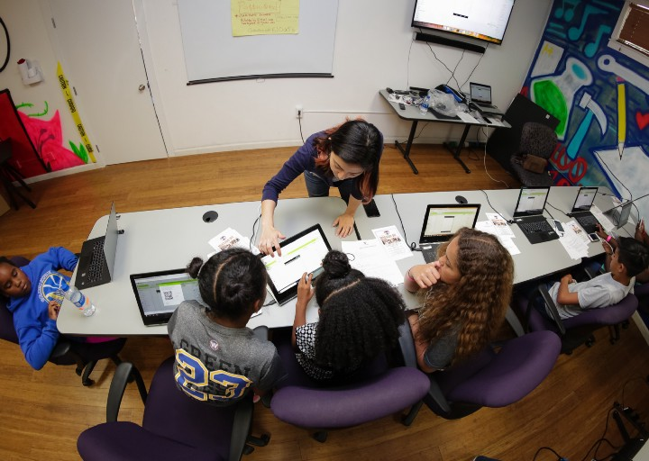 Juliana De Heer working with a group of students during a codingworkshop