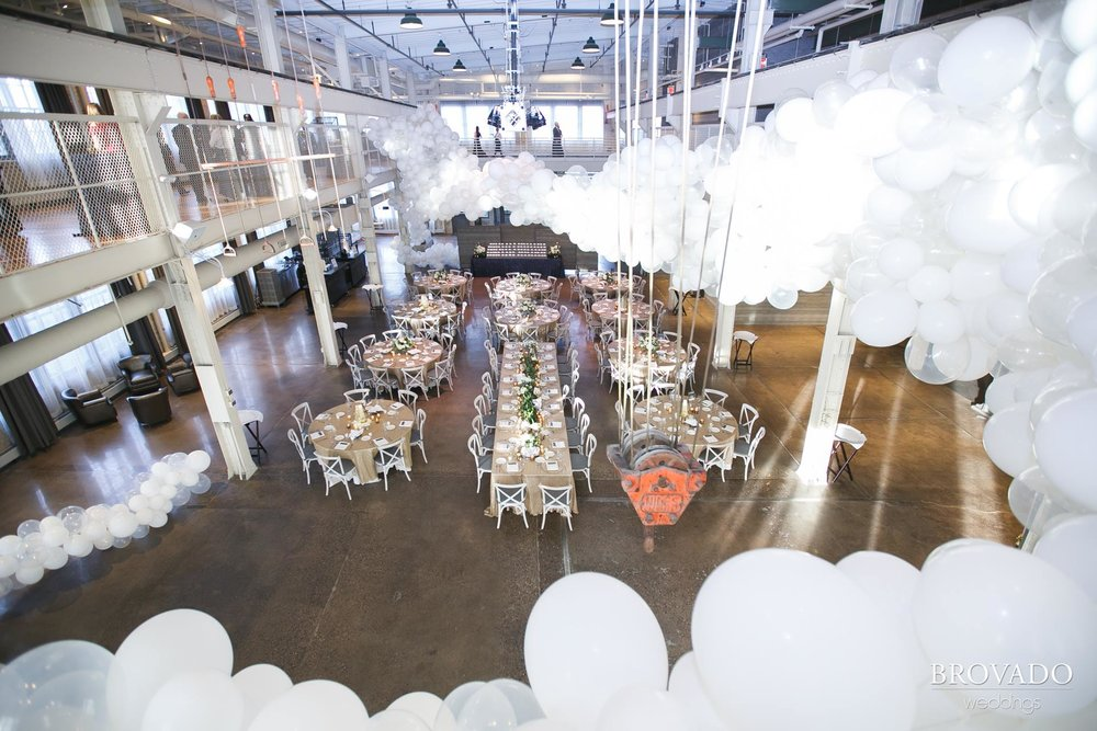 Hannah + Jason | Machine Shop Wedding | Brovado Weddings | Sixpence Events Day of Coordinating | David's Bridal Dress | Girl Friday Creative balloons arch hanging from the ceiling