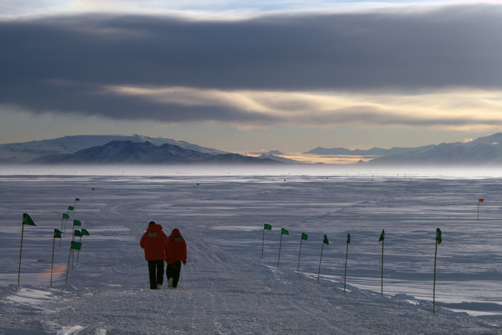 Nick Santos and Konrad Meister walking out onto the frozen waters of McMurdo Sound, Antarctica.  The MOO is hidden nearby beneath an eight-foot-thick solid cover of sea ice in the worlds southernmost accessible marine environment.
