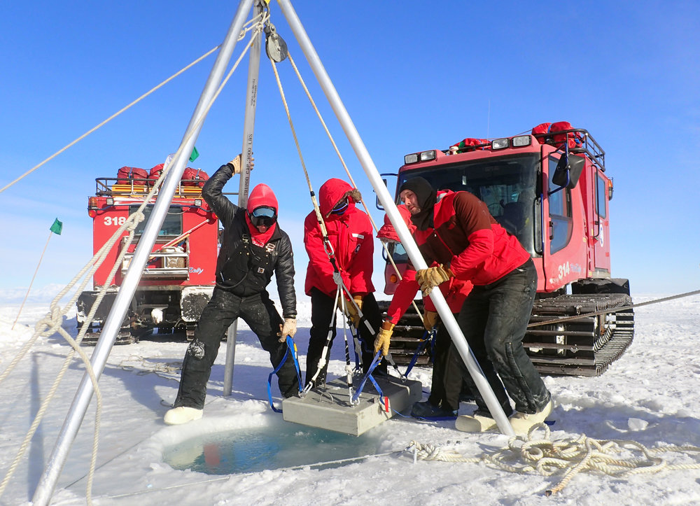 The team working together to sending the concrete anchor blocks to the bottom of the sea through eight feet (2.5m) of sea ice.  Four concrete blocks, weighing from 200 to 3,500 pounds (90 to 1,500 kg), make up the anchoring system for the MOO's scientific instruments in this harsh environment. Without these (or even with) the MOO could be knocked over in dangerous ocean swells, floated away by accumulating anchor ice, or pushed around by the small icebergs that venture into the shallows around our research site.