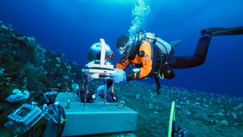 Paul Cziko placing the HD video camera, with it's self-cleaning glass dome, on the anchor block . All electrical connections for the MOO were made wet, with cold hands wrapped inside greasy dry gloves. Any mistakes in making these critical matings could have resulted in rapid system failure–an untenable result given that replacement parts can take weeks or months to arrive in this remote location.