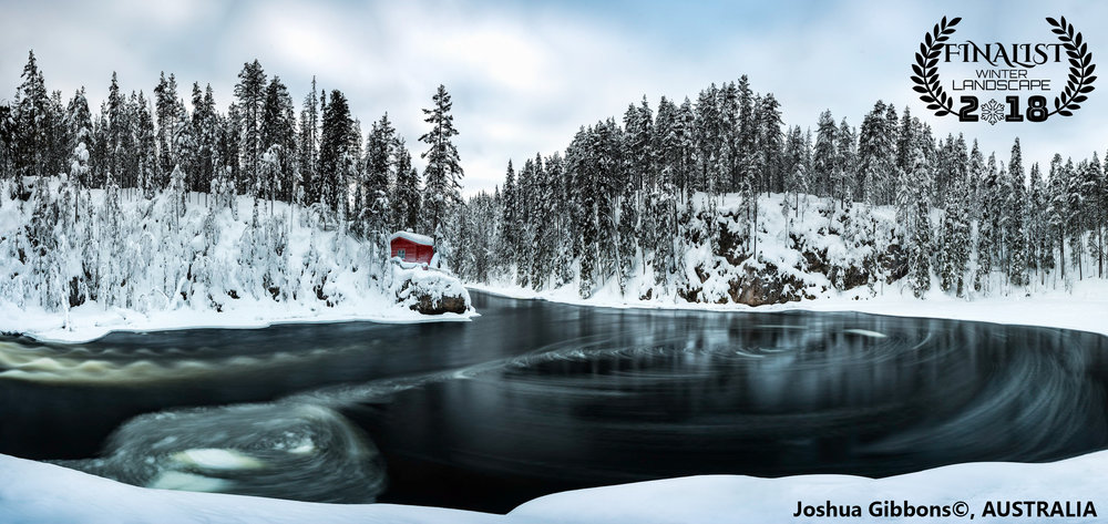 "'Isolation'  ""A traditional log cabin sits in solitude on the Kitkajoki River, Finland. The unique shape of the riverbend causes ice to swirl and spiral its way through the frozen forest.""  Photographer: Joshua Gibbons, AUSTRALIA"