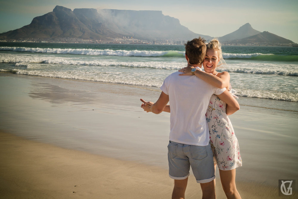 An engaged couple share a dance on a beach in Cape Town