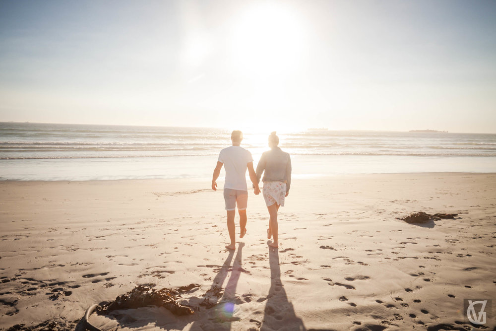 An engaged couple walk off into the sunset together