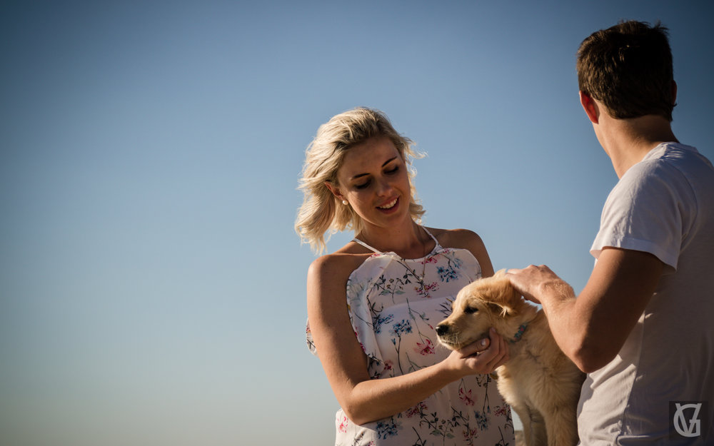 An engaged couple on the beach with their puppy in Cape Town