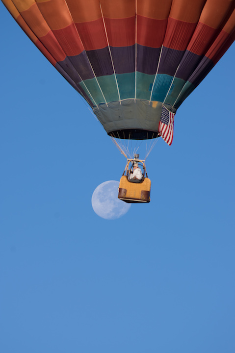 A balloonist floats past an almost full moon during the 2nd day of mass ascension when 400+ balloons simultaneously take off.