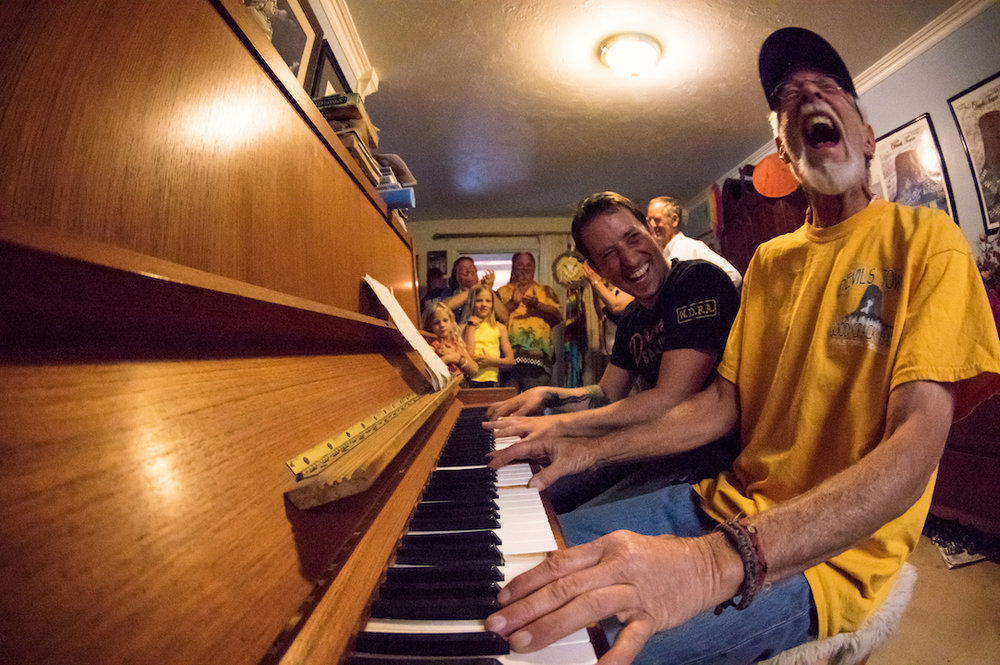 Frank Sanders (right) plays an impromptu duet with a guest in the Lodge living room. A crack climbing legend in his own right, Frank keeps his fingers nimble by daily piano practice and performances.