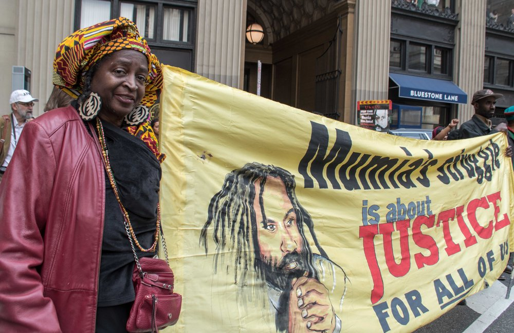 Philadelphia, Apr 18, 2019 - Press Conference for Mumia Abu-Jamal. Nana Njinga with banner. (photo credit: Joe Piette)