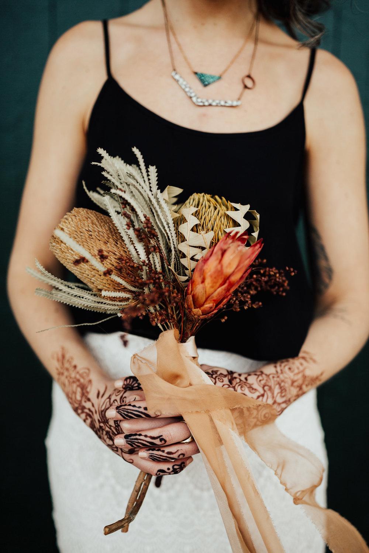 rust chiffon silk ribbon and soft pink habotai silk ribbon wrapped around a dried protea bouquet by Birch Affair, henna by Kelly Caroline