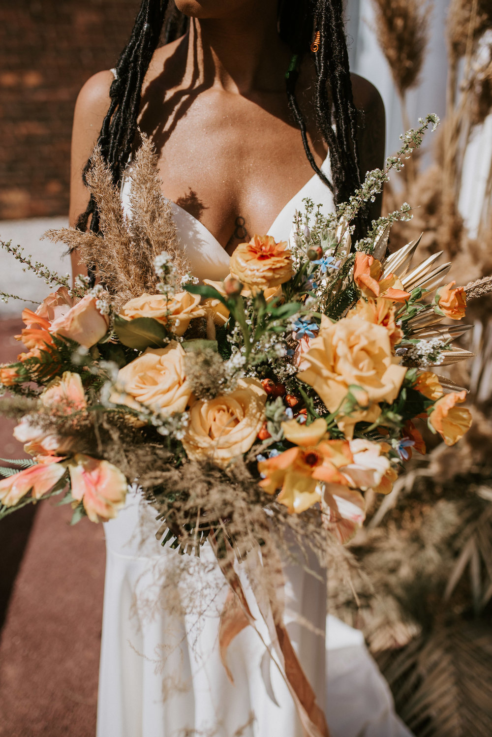 Nadia in her Detroit Bridal House gown holding her sprawling bridal bouquet. Features    rust    &    sand    colored silk ribbons by Rosemarine Textiles.