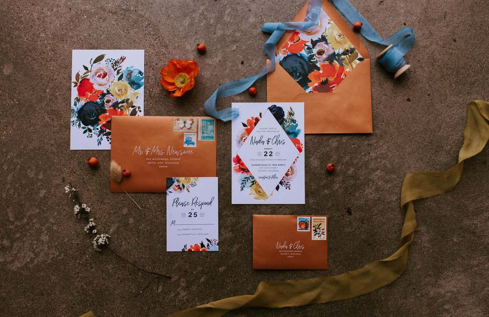 """A flat lay featuring watercolor invitations designed by    Invitations By Caitlin   . Shown here is Rosemarine Textiles 2"""" wide deep chartreuse silk ribbon in chiffon and 1"""" wide light indigo ribbon in chiffon."""