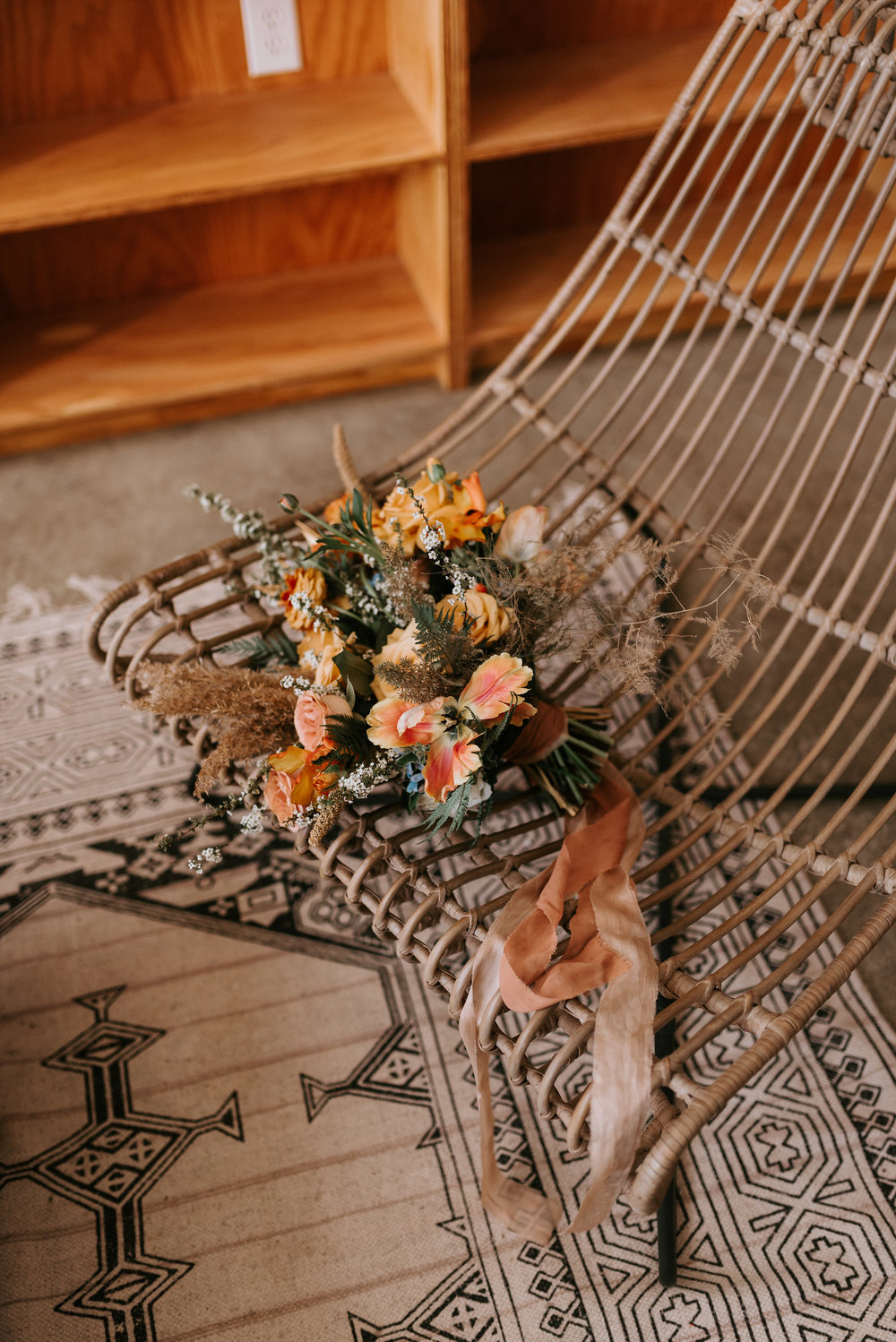 """The lovely bridal bouquet featuring our    2"""" wide habotai silk sand    colored ribbon and    2"""" wide rust chiffon ribbon."""