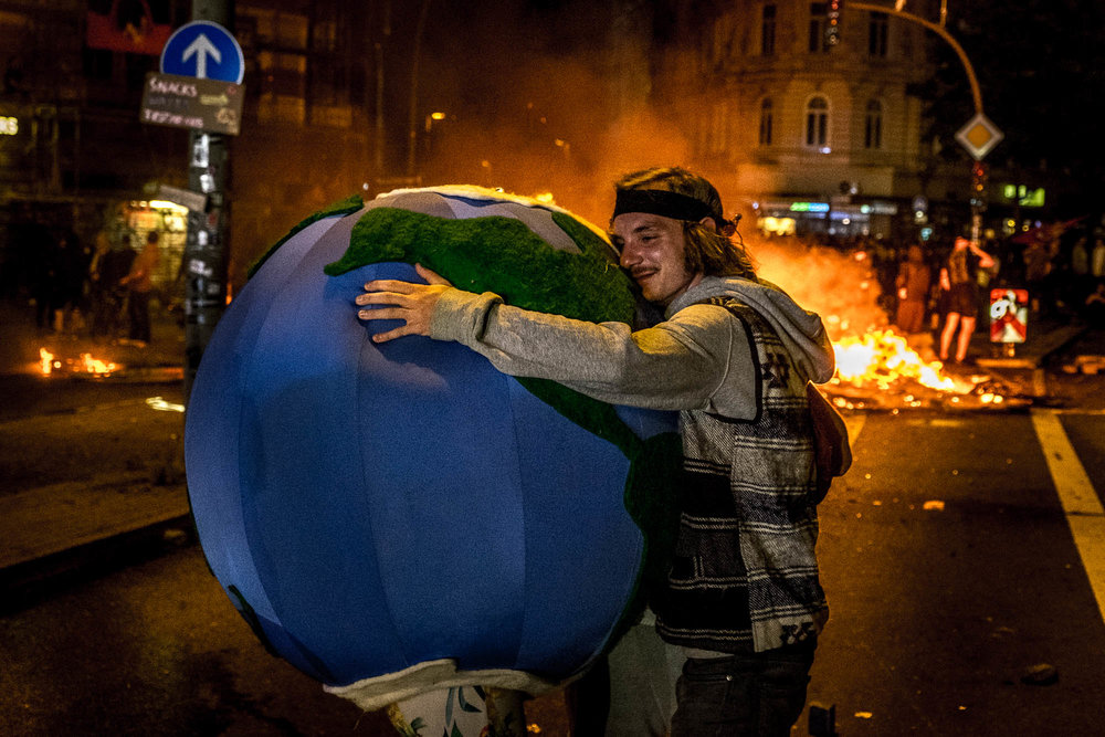 A young man hugs a girl that is dressed like a globe. They show their love for the world and demonstrate that effective protest does not have to be violent.