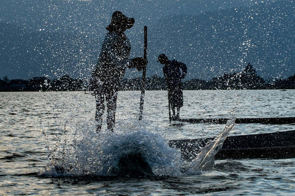 Fishermen beating with long sticks into the water to drive the fish into their nets. Bagan, Myanmar..