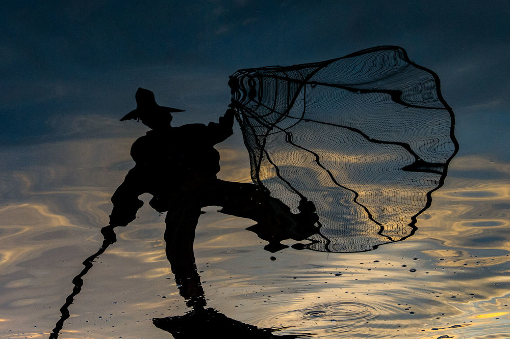 Fisherman holding up his net with one leg. Inle Lake, Myanmar.