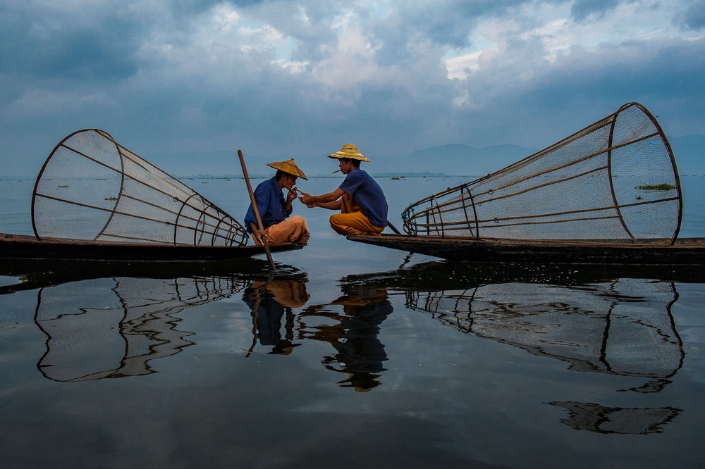 Two fishermen taking a a break to smoke a cigarette. Inle Lake, Myanmar.