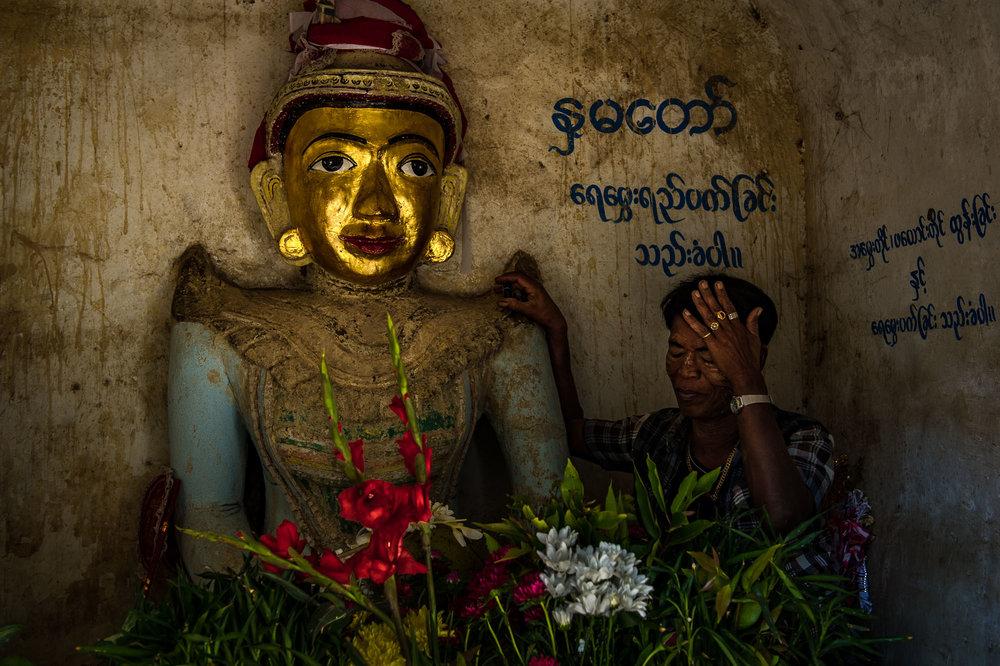 Man worshiping a Buddha statue. Bagan,Myanmar.