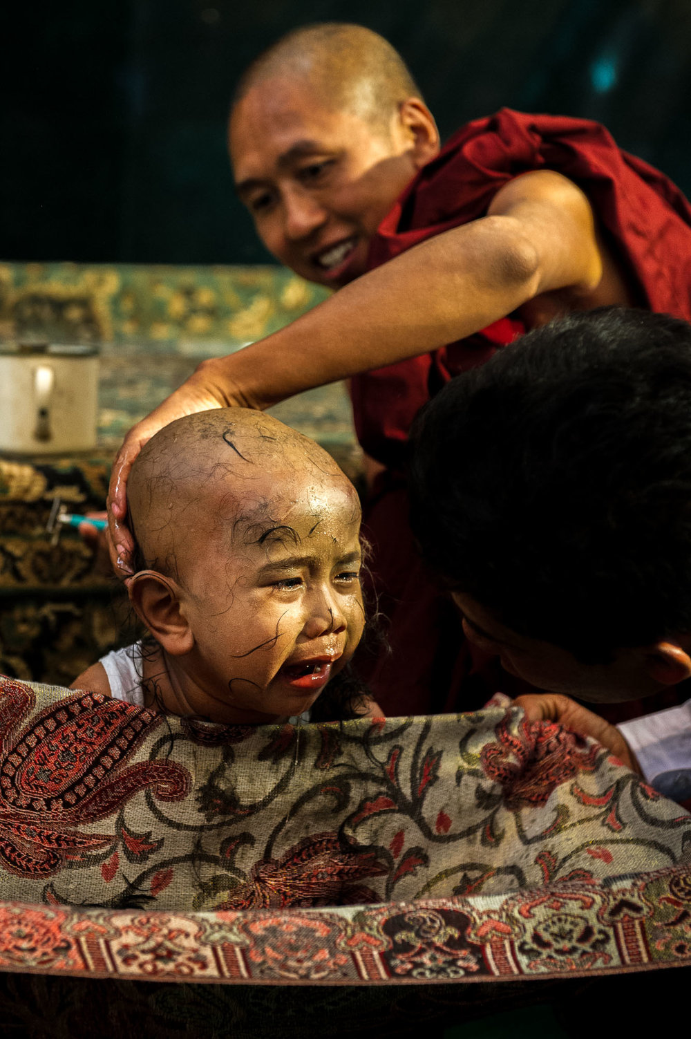 Young boy cries of fear and pain during the initiation ceremony for becoming a novice monk. In Myanmar it is customary for every young boy to enter a Buddhist monastery. Bagan, Myanmar.