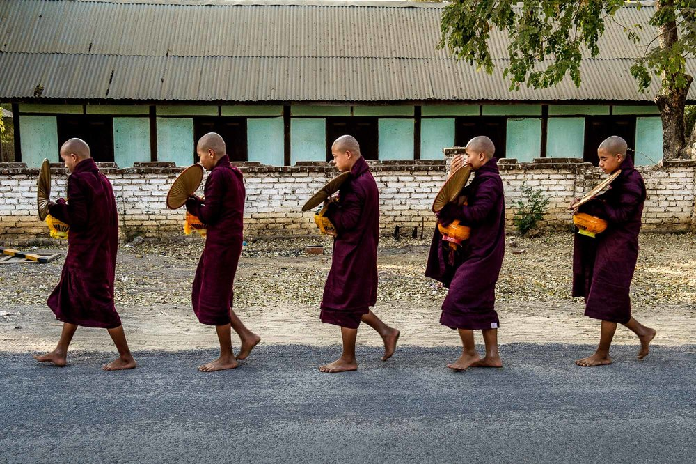 Monks on their daily tour through the vicinity of their monastery asking for food. Bagan, Myanmar.