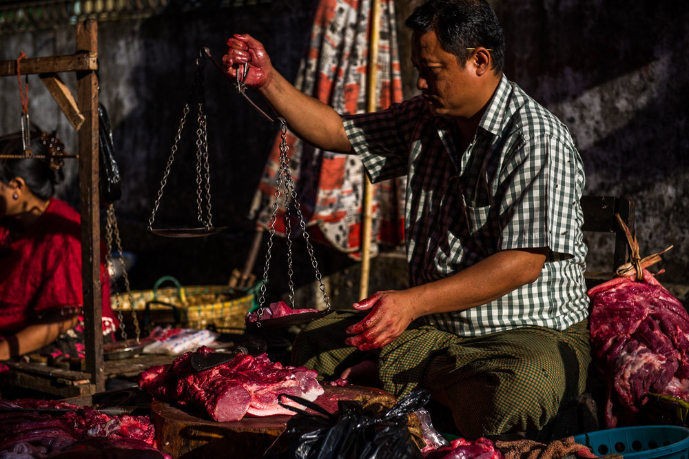 Butcher selling fresh meat on a street market. Bagan, Myanmar.