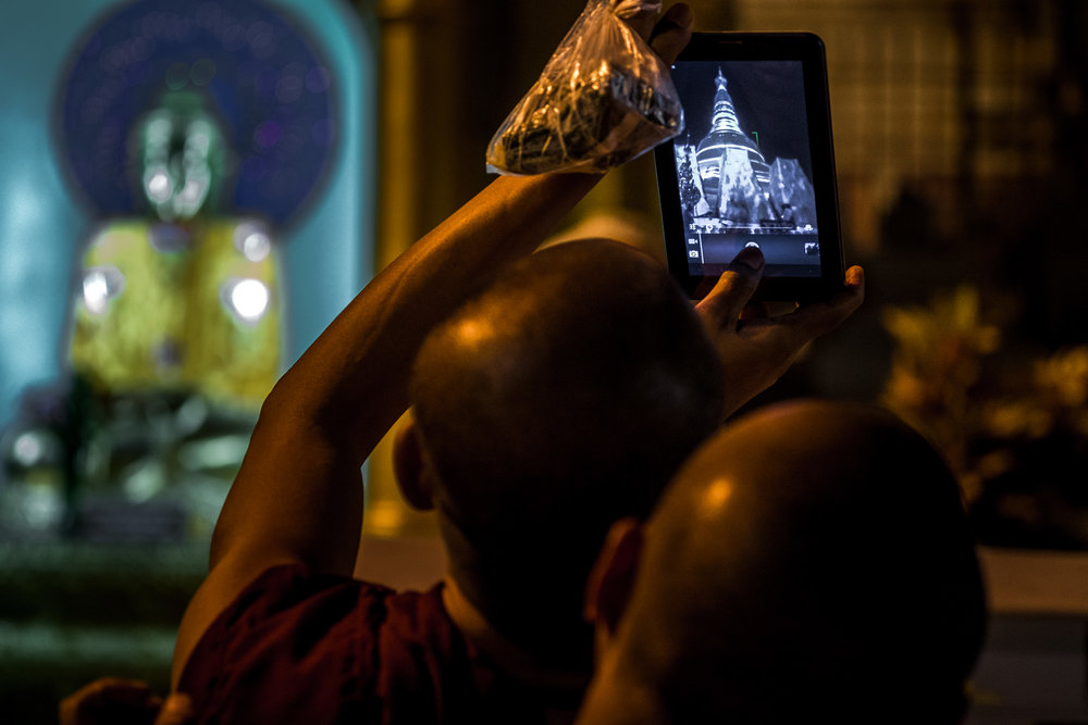 Young monk taking picture with his iPad of Shwedagon Pagoda, the most sacred Buddhist pagoda in Myanmar and the largest gold pagoda in the world. Yangon, Myanmar.