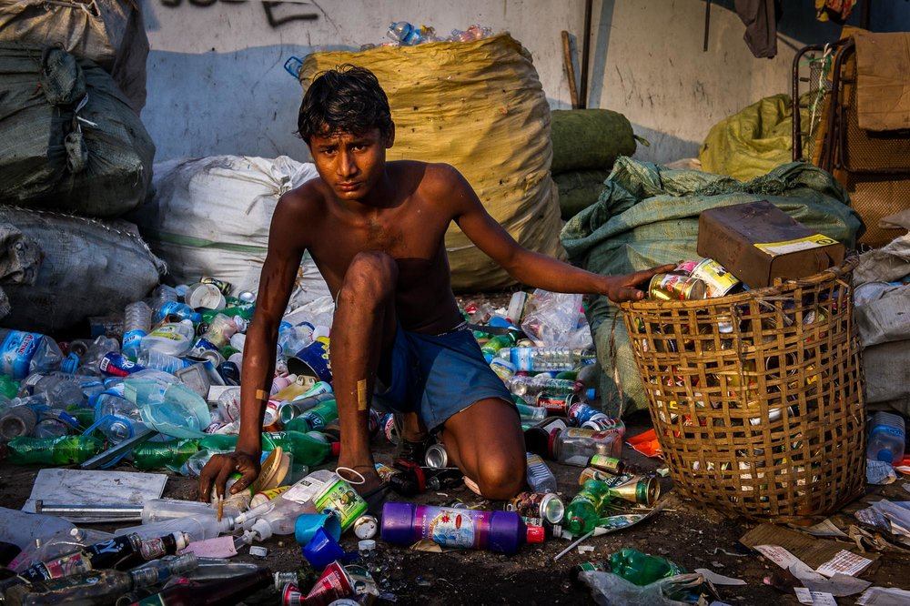 Young man gathering rubbish of a street market. Yangon, Myanmar.