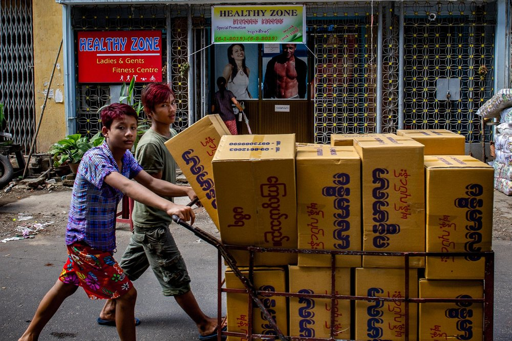 "Young workers pass by a ""Healthy Zone Fitness Centre"". Yangon, Myanmar."