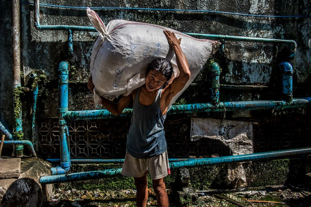 Man carrying a large sack in the hot sun and high humidity of the city. Yangon, Myanmar.