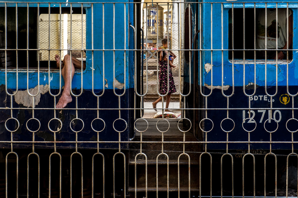 Man sticking his leg out of the window of a train. Yangon, Myanmar.