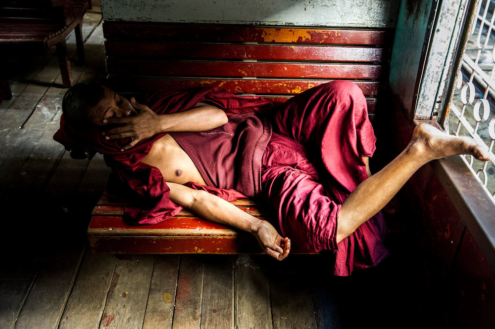 Monk resting on the bench of a train. Yangon, Myanmar.