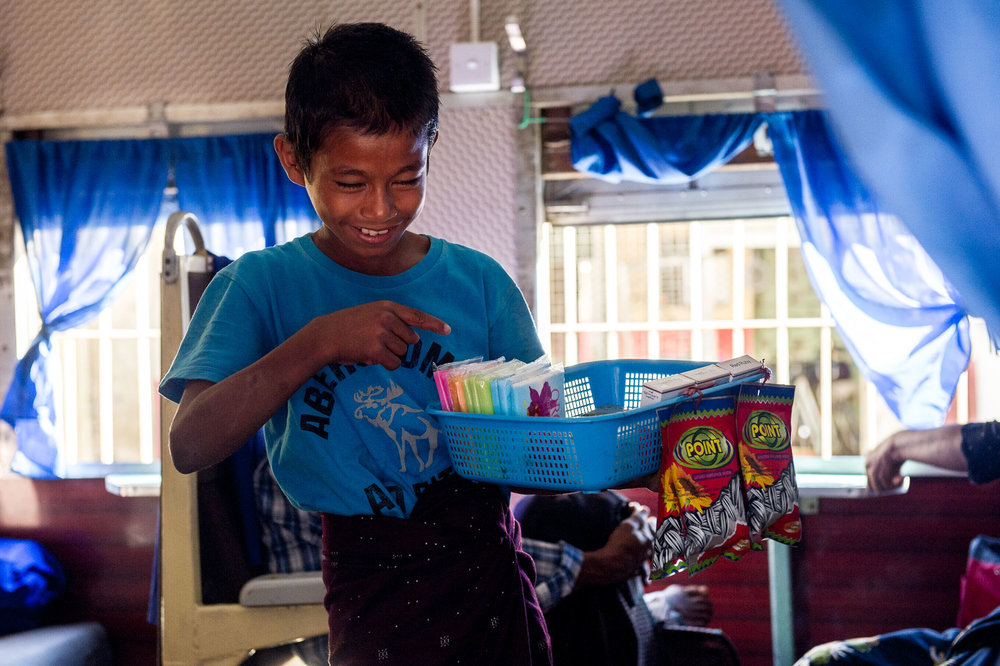 Young boy selling tissues, cigarettes, and other small items to travelers in a waiting train. Yangon, Myanmar.