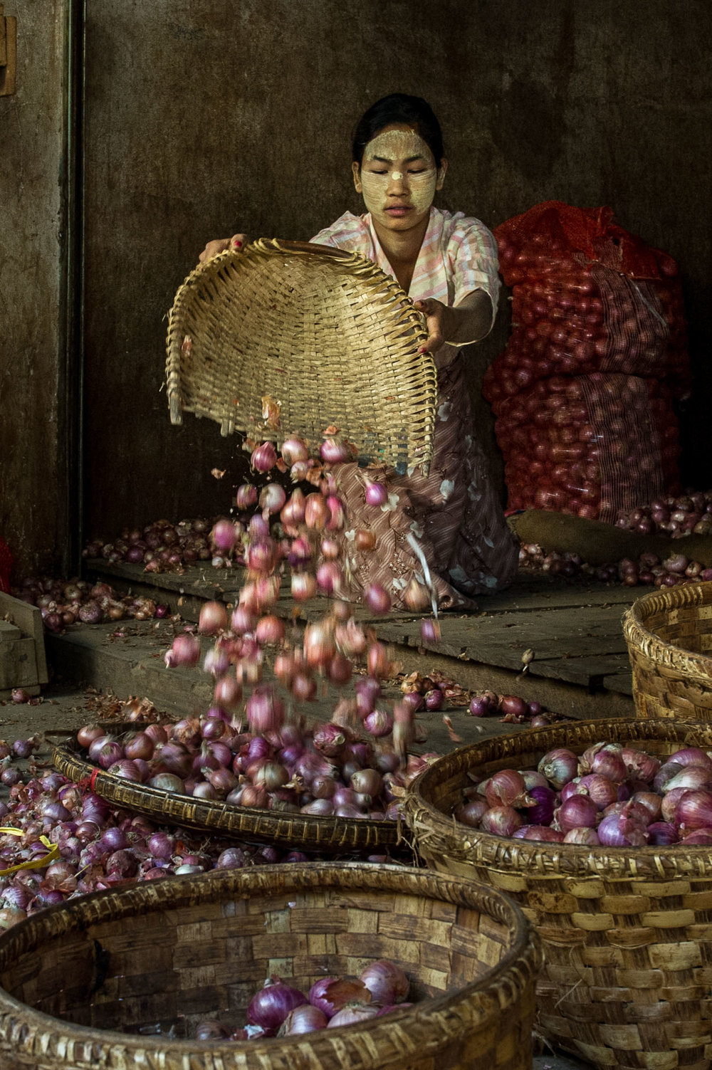 Female market vendor cleaning onions by throwing them from one basket to another. Bagan, Myanmar.