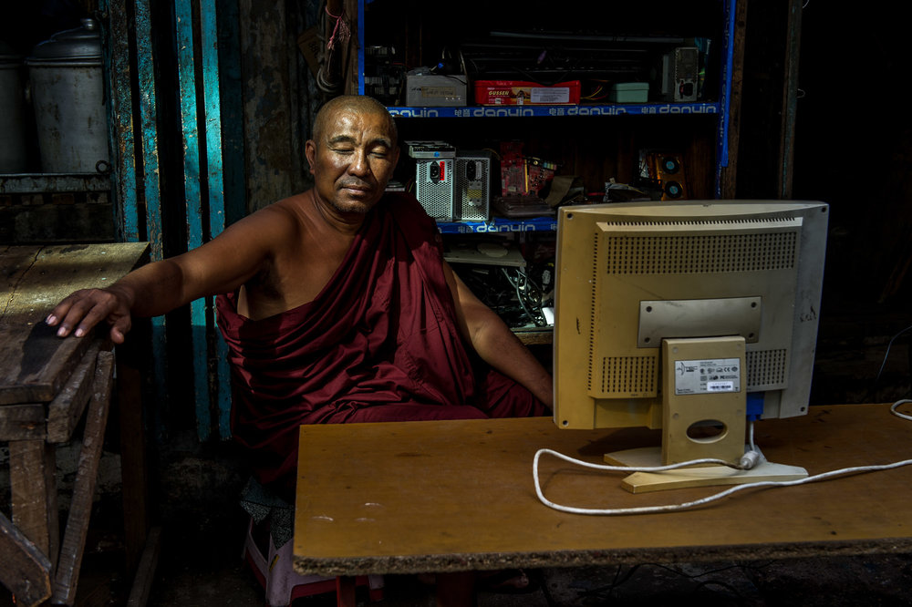 Monk sitting on a porch in front of an outdated desktop computer. Yangon, Myanmar.