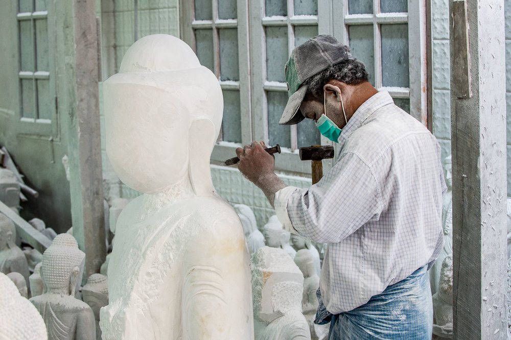 Marble stone craftsman chiseling the neck of a Buddha statue. Mandalay, Myanmar.