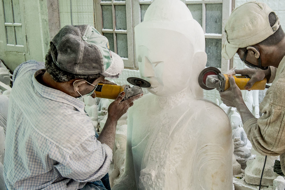 Craftsman cutting the smile into the face of a marble Buddha statue. Mandalay, Myanmar.