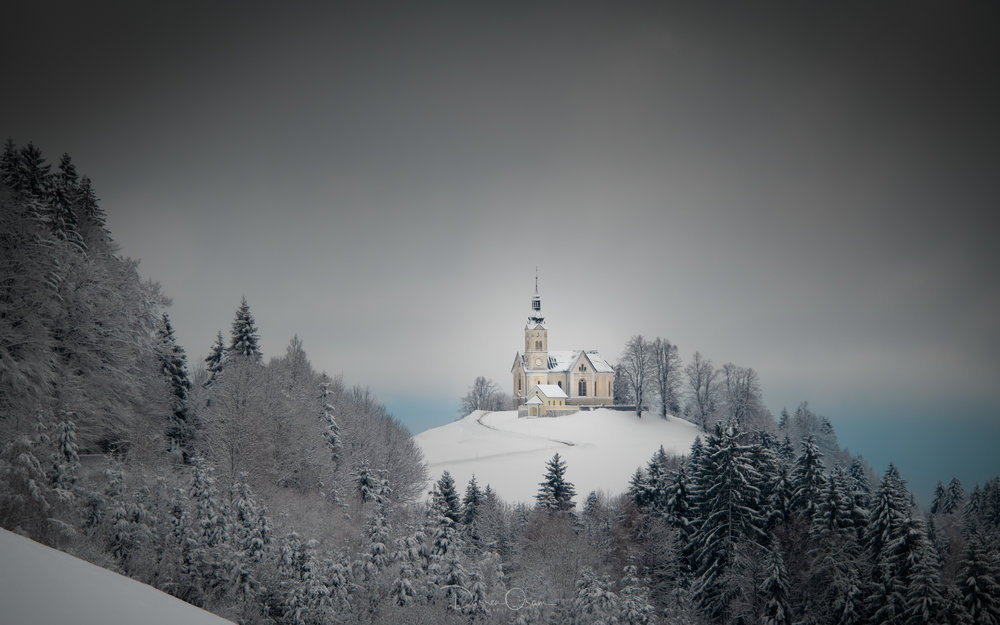 The Church of Saint Leonard in Črni Vrh in the snow