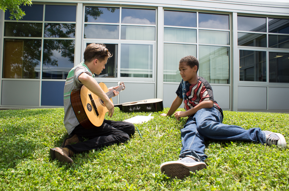 Graham teaching a middle school student how to play the guitar.