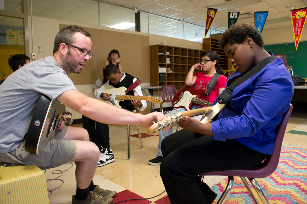 Mark Thompson teaches chords to a middle school student.